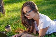 Mujer joven que usa el ordenador portátil en el parque que miente en la hierba verde Concepto de la actividad del tiempo libre Imagen de archivo libre de regalías