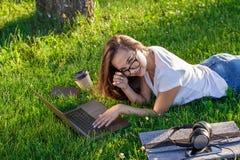 Mujer joven que usa el ordenador portátil en el parque que miente en la hierba verde Concepto de la actividad del tiempo libre Fotografía de archivo