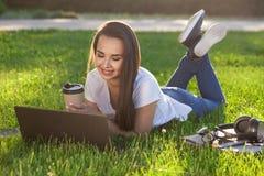 Mujer joven que usa el ordenador portátil en el parque que miente en la hierba verde Concepto de la actividad del tiempo libre Imagen de archivo