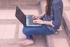Mujer joven que usa el ordenador portátil en pasos al aire libre Imagen de archivo libre de regalías