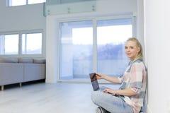 Mujer joven que usa el ordenador portátil en el piso Imagenes de archivo
