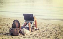 Mujer joven que usa el ordenador portátil en una playa Trabaja independientemente la estafa del trabajo Imágenes de archivo libres de regalías