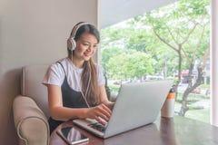 Mujer joven que usa el ordenador portátil, listenning a la música Imagenes de archivo