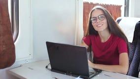 Mujer joven que usa el ordenador portátil que se sienta en tren almacen de video