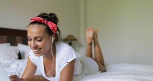 Mujer joven que usa el ordenador portátil que tiene mentira que habla de la charla de la muchacha hermosa video de la llamada en  almacen de metraje de vídeo