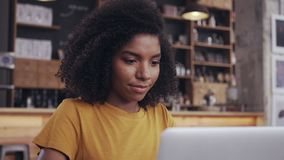 Mujer joven que usa el ordenador port?til en caf? almacen de metraje de vídeo