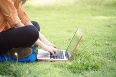 Mujer joven que usa el ordenador sobre los vidrios verdes en el parque Foto de archivo