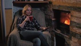 Mujer joven que usa el Tablet PC de Digitaces y disfrutando de la bebida caliente del invierno que se sienta por la chimenea en c almacen de video