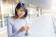 Mujer joven que usa el teléfono celular Imagen de archivo libre de regalías