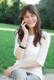 Mujer joven que usa el teléfono celular fotografía de archivo