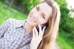 Mujer joven que usa el teléfono celular al aire libre Foto de archivo