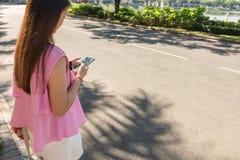 Mujer joven que usa el teléfono elegante al aire libre en mañana soleada Foto de archivo libre de regalías