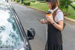 Mujer joven que usa el teléfono elegante antes de ir a trabajar Foto de archivo libre de regalías