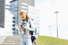Mujer joven que usa el teléfono elegante en el campus de la universidad Fotos de archivo