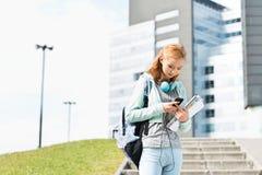 Mujer joven que usa el teléfono elegante en el campus de la universidad Foto de archivo libre de regalías