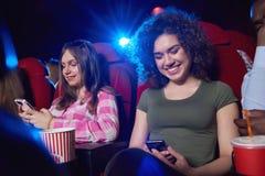 Mujer joven que usa el teléfono elegante en el cine Imagenes de archivo