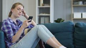 Mujer joven que usa el teléfono elegante mientras que se relaja en el sofá almacen de video