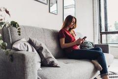 Mujer joven que usa el teléfono elegante mientras que se relaja en el sofá en la sala de estar Foto de archivo libre de regalías