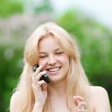Mujer joven que usa el teléfono en el parque Fotos de archivo