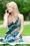 Mujer joven que usa el teléfono en el parque Fotografía de archivo libre de regalías