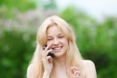 Mujer joven que usa el teléfono en el parque Fotos de archivo libres de regalías