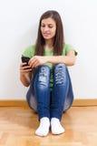 Mujer joven que usa el teléfono móvil Imagenes de archivo