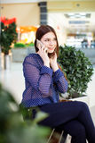 Mujer joven que usa el teléfono móvil en centro comercial Fotografía de archivo
