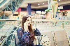 Mujer joven que usa el teléfono móvil en centro comercial Fotografía de archivo libre de regalías