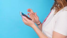 Mujer joven que usa el teléfono móvil en fondo azul del color almacen de metraje de vídeo