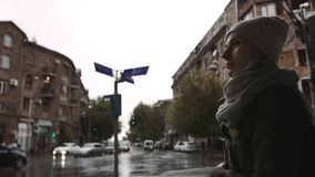 Mujer joven que usa el teléfono móvil en la calle en una tarde lluviosa en la ciudad metrajes