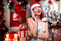Mujer joven que usa el teléfono móvil en la Navidad Foto de archivo