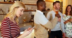 Mujer joven que usa el teléfono móvil mientras que los amigos están teniendo bebida 4K 4k almacen de video
