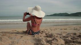 Mujer joven que usa el teléfono móvil mientras que toma el sol en la playa La muchacha hermosa en un sombrero del bikini y del so metrajes