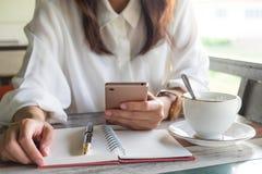 Mujer joven que usa el teléfono móvil para comprobar algo mientras que pluma Fotografía de archivo libre de regalías