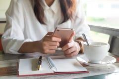 Mujer joven que usa el teléfono móvil para comprobar algo mientras que pluma Imagen de archivo libre de regalías
