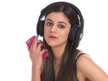 Mujer joven que usa el teléfono móvil para escuchar la música Imagen de archivo