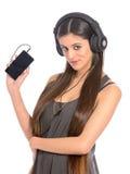 Mujer joven que usa el teléfono móvil para escuchar la música Fotografía de archivo