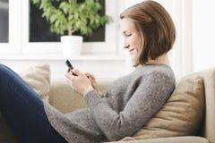 Mujer joven que usa el teléfono móvil que se relaja en el sofá Fotos de archivo