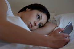 Mujer joven que usa el teléfono que miente en su cama Fotografía de archivo libre de regalías