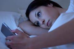 Mujer joven que usa el teléfono que miente en cama Foto de archivo libre de regalías
