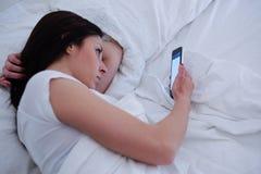 Mujer joven que usa el teléfono que miente en cama Imágenes de archivo libres de regalías