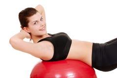 Mujer joven que usa la bola del ejercicio Imagen de archivo libre de regalías