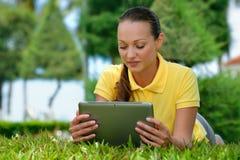 Mujer joven que usa la colocación al aire libre de la tablilla en hierba Imágenes de archivo libres de regalías