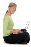 Mujer joven que usa la computadora portátil Foto de archivo