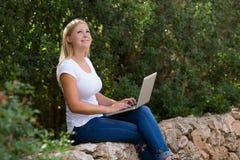 Mujer joven que usa la computadora portátil al aire libre Imagen de archivo libre de regalías