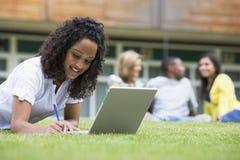 Mujer joven que usa la computadora portátil en césped del campus Imagen de archivo