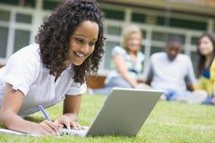 Mujer joven que usa la computadora portátil en césped del campus imágenes de archivo libres de regalías