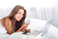 Mujer joven que usa la computadora portátil en cama imagen de archivo