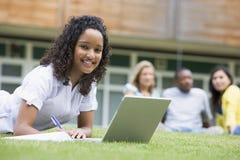 Mujer joven que usa la computadora portátil en campus Foto de archivo libre de regalías