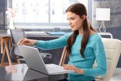 mujer joven que usa la computadora portátil en el país Imagenes de archivo